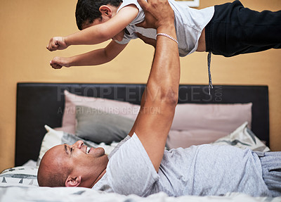 Buy stock photo Cropped shot of a cheerful young man lifting up his son in the air to fly like a super hero while lying down on a bed at home during the day