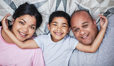 Buy stock photo Portrait of a cheerful young family lying down and hanging out in bed smiling all the way at home during the day