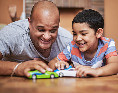 Buy stock photo Cropped shot of a cheerful little boy and his father playing with toy cars while being seated on the floor at home during the day