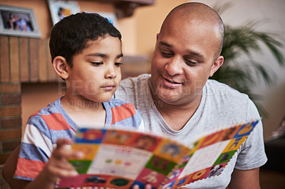 Buy stock photo Cropped shot of a cheerful little boy and his father reading a storybook together at home during the day