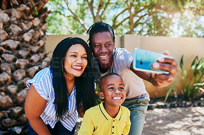 Buy stock photo Cropped shot of a happy young family of three taking a selfie in their backyard at home