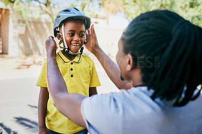 Buy stock photo Cropped shot of an affectionate young single father adjusting his son's helmet before he rides a bike outdoors