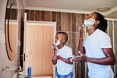 Buy stock photo Shot of a father teaching his little son how to shave in the bathroom at home