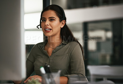 Buy stock photo Shot of a young call centre agent working on a computer in an office