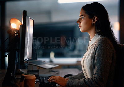 Buy stock photo Shot of a young businesswoman working on a computer in an office at night
