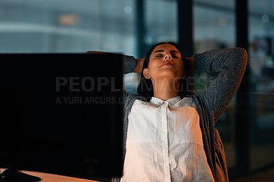 Buy stock photo Shot of a young businesswoman taking a break while working in an office at night