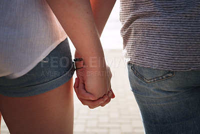 Buy stock photo Cropped shot of an unrecognizable couple holding hands while on a date together outdoors