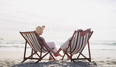 Buy stock photo Full length shot of an affectionate senior couple relaxing on loungers at the beach on a summer's day