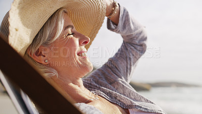 Buy stock photo Cropped shot of an attractive senior woman relaxing on a lounger on a summer's day at the beach