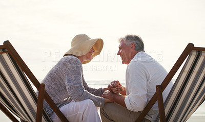 Buy stock photo Cropped shot of an affectionate senior couple holding hands intimately while sitting on loungers at the beach