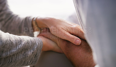 Buy stock photo Cropped shot of an unrecognizable senior couple holding hands intimately while sitting at the beach