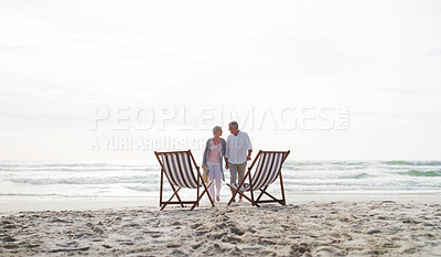 Buy stock photo Full length shot of an affectionate senior couple walking towards their loungers at the beach during the day