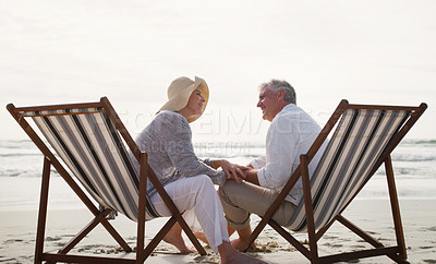 Buy stock photo Full length shot of an affectionate senior couple having an intimate chat while sitting on loungers at the beach