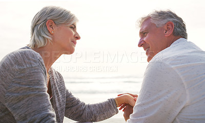 Buy stock photo Cropped shot of an affectionate senior couple having an intimate chat while sitting on loungers at the beach