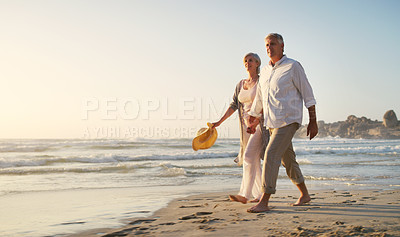 Buy stock photo Full length shot of an affectionate senior couple walking along the beach at sunset