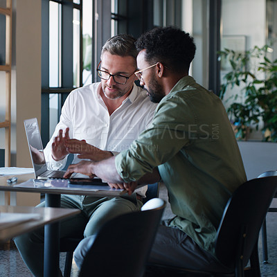 Buy stock photo Shot of two businessmen using a laptop and having a discussion in a modern office