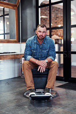 Buy stock photo Full length shot of a handsome mature barber sitting on a chair inside his barbershop