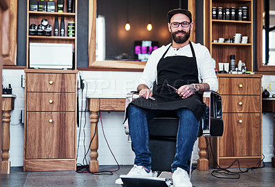 Buy stock photo Full length shot of a handsome young barber sitting on a chair inside his barbershop