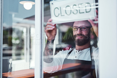 Buy stock photo Cropped shot of a handsome young barber hanging up a closed sign on the window of his barbershop