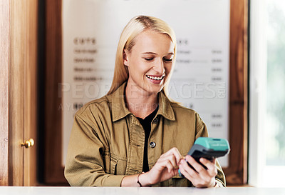 Buy stock photo Cropped shot of an attractive young hairdresser using a card machine inside her salon