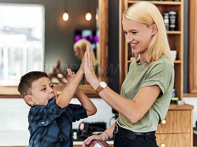 Buy stock photo Cropped shot of an adorable little boy giving his hairdresser a high five inside a salon