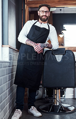 Buy stock photo Full length shot of a handsome young barber posing with his arms folded inside a barbershop