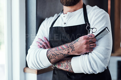 Buy stock photo Cropped shot of a unrecognizable tattooed barber posing with a pair of scissors and a hair comb inside a barbershop