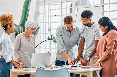 Buy stock photo Cropped shot of a diverse group of businesspeople standing together and brainstorming over paperwork in the office
