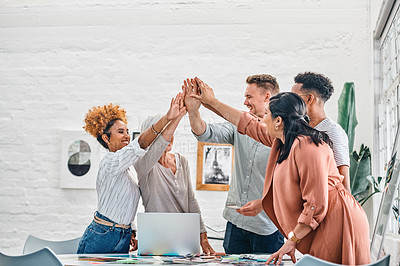 Buy stock photo Cropped shot of a diverse group of businesspeople standing and giving each other a high five after a successful meeting
