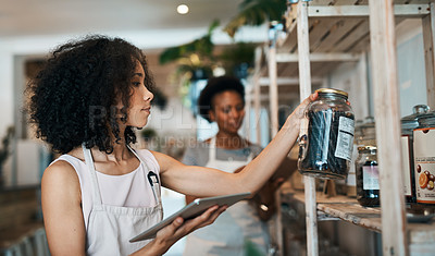 Buy stock photo Shot of a young woman using a digital tablet while doing inventory in a waste free store