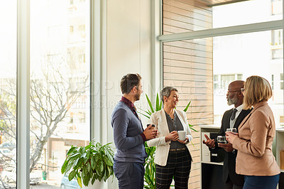 Buy stock photo Shot of a group of businesspeople standing together while having a discussion in a modern office