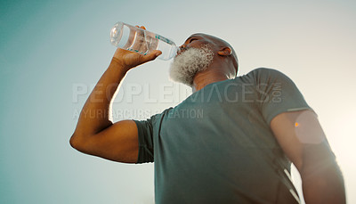 Buy stock photo Low angle shot of a senior man standing alone and drinking water after a workout in his back garden