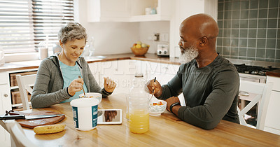 Buy stock photo Cropped shot of a senior couple sitting together in their kitchen for breakfast at home