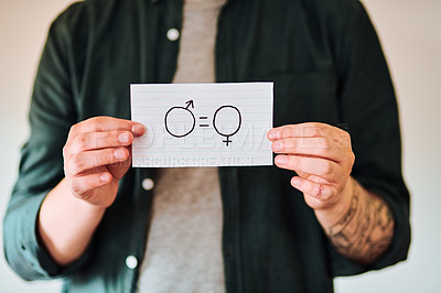 Buy stock photo Cropped shot of an  unrecognizable man holding a piece of paper with gender equality symbols indoors