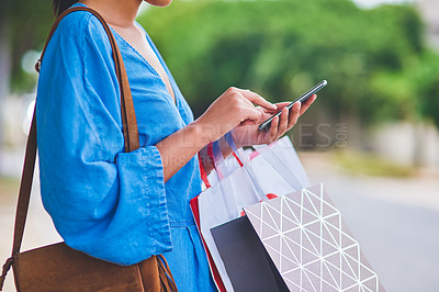 Buy stock photo Cropped shot of an unrecognizable woman using a smartphone while holding shopping bags in the city during the day