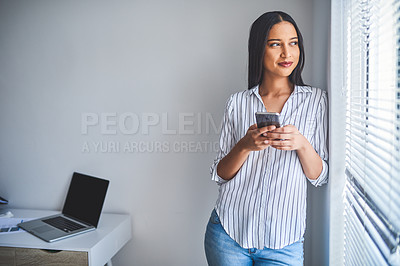 Buy stock photo Cropped shot of an attractive young businesswoman standing alone and using her cellphone in her home