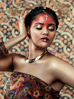 Buy stock photo Cropped shot of an attractive young woman dressed in traditional attire and makeup posing against a patterned background