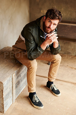 Buy stock photo Shot of a handsome young man sitting on a wooden box outside