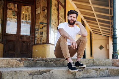 Buy stock photo Shot of a handsome young man sitting on the steps of a rustic building