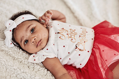 Buy stock photo High angle portrait of an adorable baby girl lying down wearing a dress that says