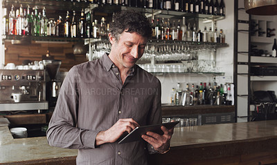 Buy stock photo Cropped shot of a man using a digital tablet in his coffee shop