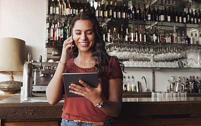 Buy stock photo Shot of a cafe owner talking on her cellphone while using a digital tablet