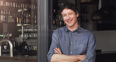 Buy stock photo Cropped shot of a man standing with his hands crossed in the doorway of his cafe