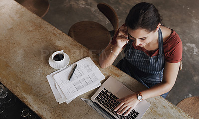 Buy stock photo High angle shot of a woman using her cellphone, laptop and doing paperwork in her cafe