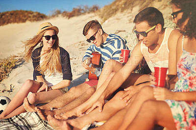 Buy stock photo Shot of a young man playing guitar for his friends while chilling at the beach