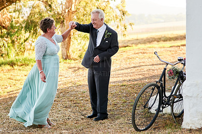 Buy stock photo Full length shot of a happy senior couple dancing together outdoors on their wedding day