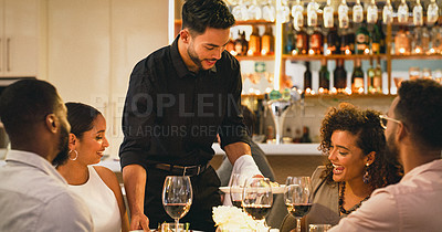 Buy stock photo Cropped shot of a handsome young waitron serving a group of friends in a restaurant