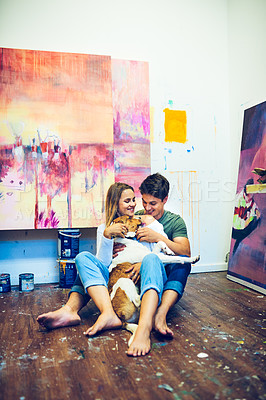 Buy stock photo Full length shot of an affectionate young couple playing with their pet dog inside their art studio