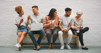 Buy stock photo Shot of a group of businesspeople using their wireless devices in the waiting room of a modern office