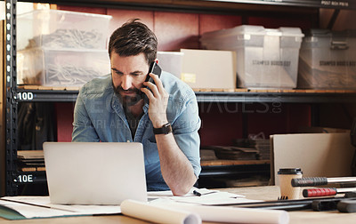 Buy stock photo Shot of a young businessman using a smartphone while designing a blueprint in a creative office